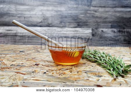 Jar With Organic Honey On Wooden Texture Background With Sprig Rosemary, And Honey Stick