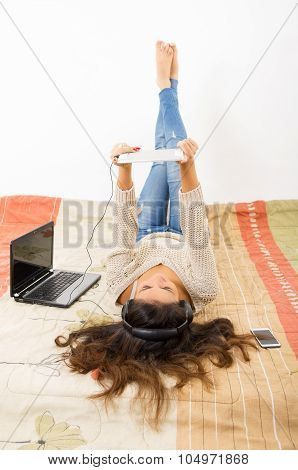 Pretty brunette wearing denim jeans white top lying down on bedsheets daydreaming with smartphone, l