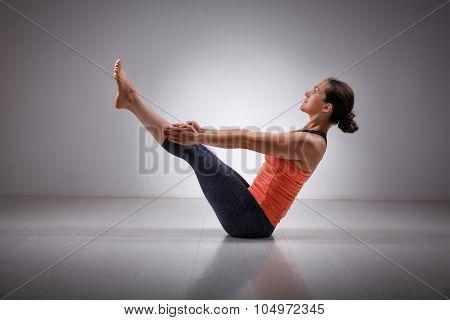 Beautiful sporty fit yogini woman practices yoga asana Paripurna navasana - boat pose