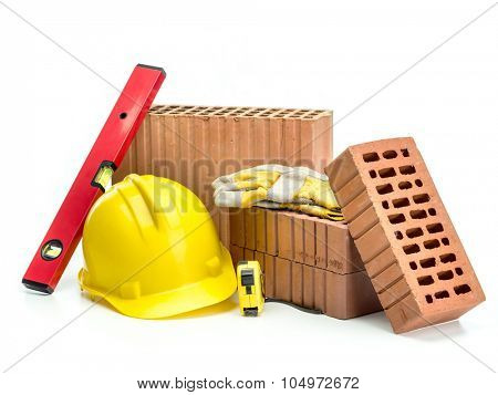 Perforated bricks, yellow helmet, protective gloves and spirit level isolated on white