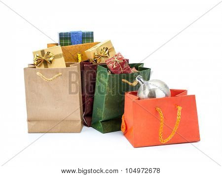 Paper christmas shopping bags with christmas presents and silver christmas ball shot on white background