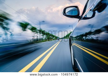 Side View Of Black Car Driving On The Country Road.