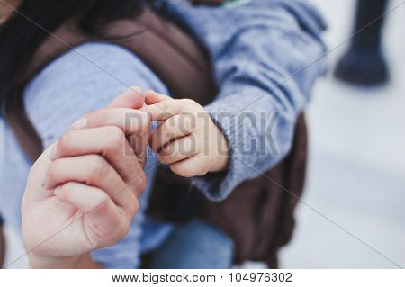 Mother Holds Her Little Son's Finger While He Is In Sling On Mother's Back