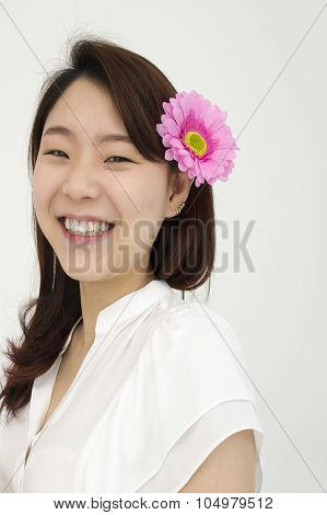 Portrait of beautiful asian woman with pink flower on ear