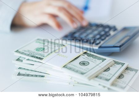 business, finance, tax and people concept - close up of woman hand counting us dollar money with calculator