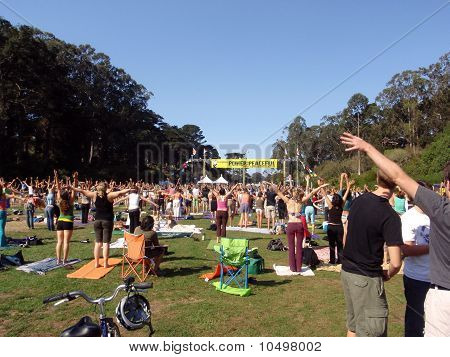 People Raise Hands Into The Air As They Stretch Out Doing Yoga Outdoors At Power To The Peaceful