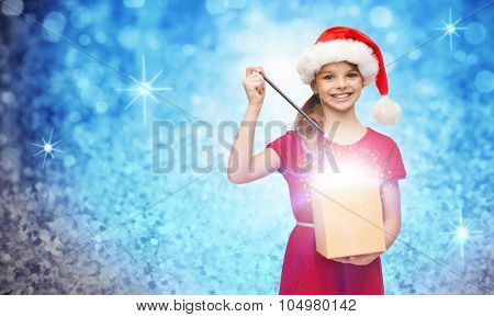 christmas, winter, holidays and childhood concept - smiling girl in santa helper hat with gift box and magic wand over blue glitter or lights background