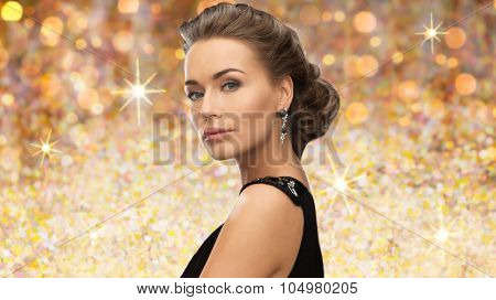 people, holidays and glamour concept - beautiful woman wearing earrings over golden lights background