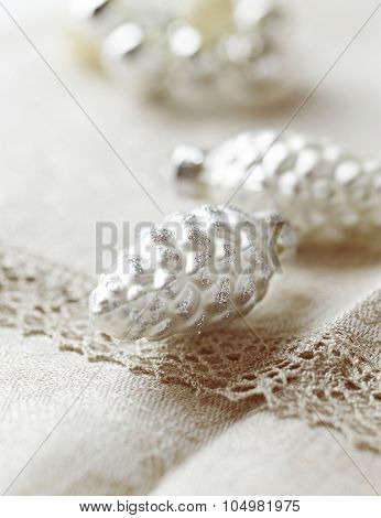 Silver cone-shaped Christmas ornaments on a linen table cloth