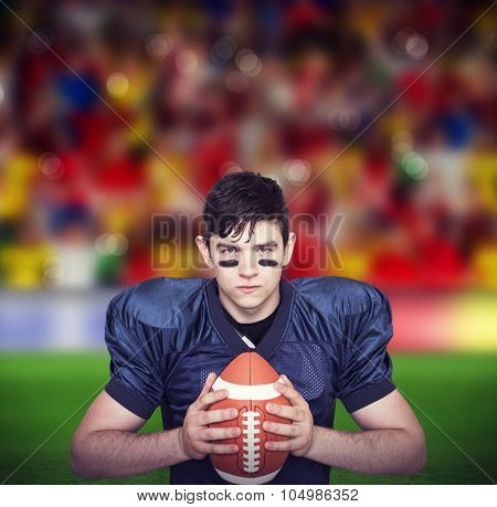 Determined american football player holding a ball against blurry football pitch with crowd