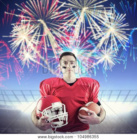 American football player holding helmet against fireworks exploding over football stadium