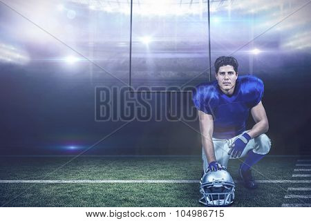 Portrait of confident American football player with hand on helmet against american football arena
