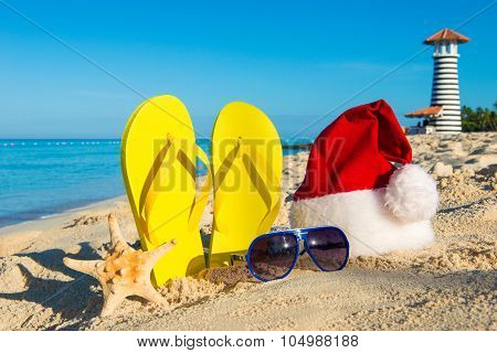 Christmas And New Year Holidays At The Sea. Santa Hat, Sandals, Sunglasses On Sandy Beach