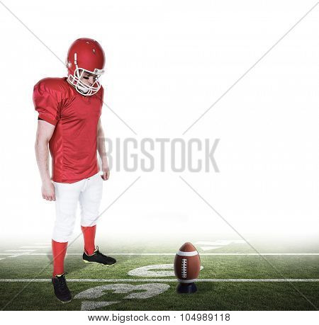 Unsmiling american football player looking down against american football pitch