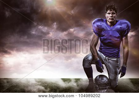 Portrait of confident American football player holding helmet while hand on knee against gloomy sky
