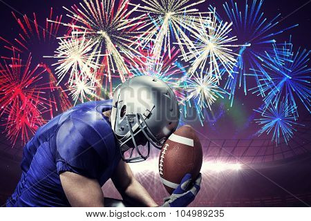 Upset American football player with ball against fireworks exploding over football stadium