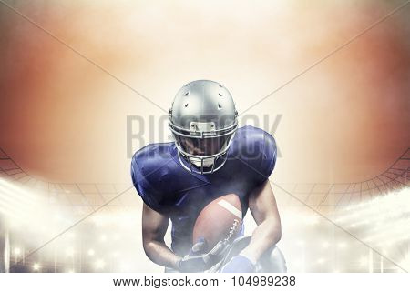 American football player holding ball while kneeling against rugby stadium