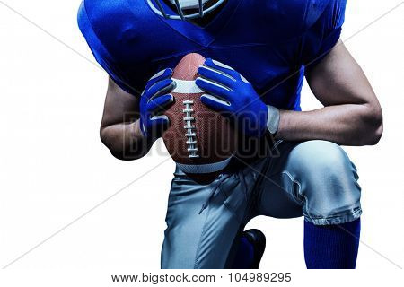 Mid section of American football player kneeling while holding ball against black background