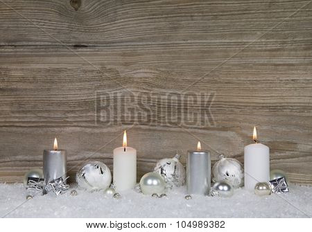 Four burning advent candles on brown wooden background for christmas decoration in shabby style.