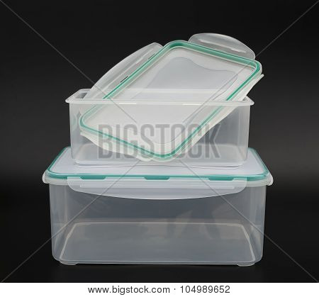 Translucent Storage Boxes With One Opened On A Black Background
