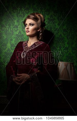 Woman In Vintage Clothes On Green Rococo Pattern Background