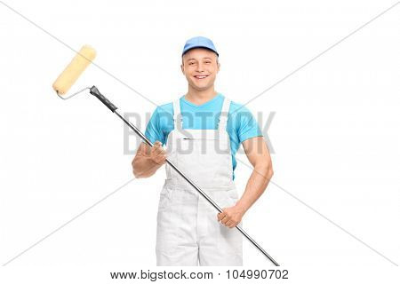 Young male decorator in a white overalls holding a paint roller and looking at the camera isolated on white background