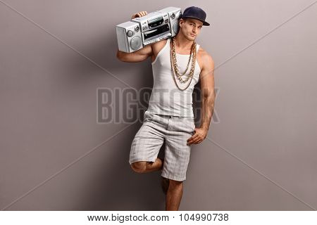 Young man in hip-hop clothes carrying a ghetto blaster over his shoulder and leaning against a gray wall