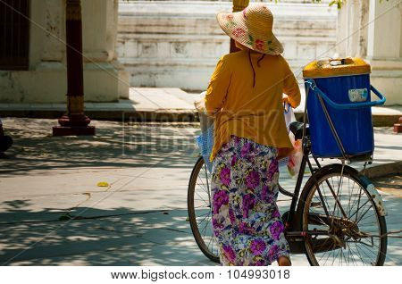Asian Woman With Bycicle And Hat