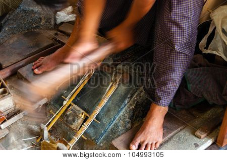 Young Craftsman Punching Gold With A Hammer