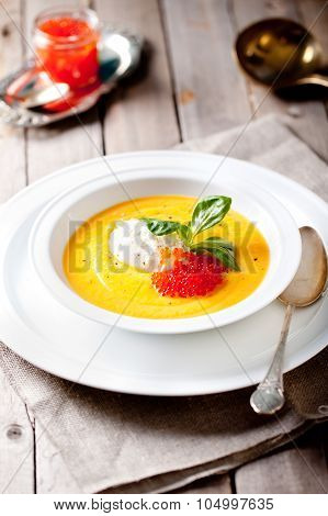 Pumpkin soup with cream and red salmon caviar