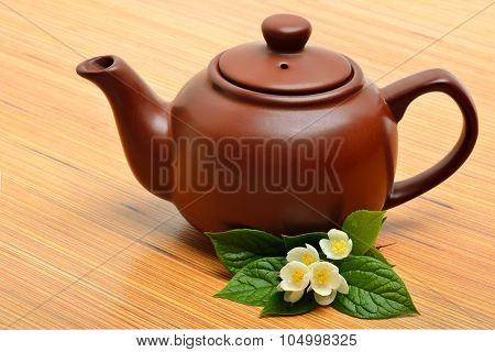 Teapot And Jasmine Flower Twig On Wooden Background