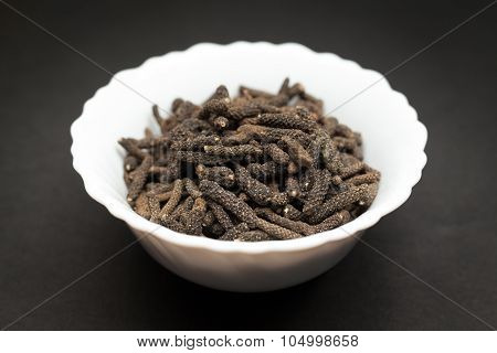 Organic Long pepper in white bowl.