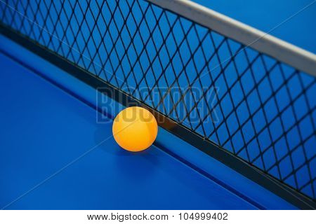 Yellow Ball Hits The Bottom Of The Net On A Blue Pingpong Table