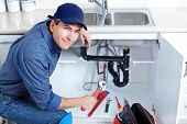 picture of plumber  - Mature plumber fixing a sink at kitchen - JPG