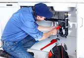 stock photo of sanitation  - Mature plumber fixing a sink at kitchen - JPG