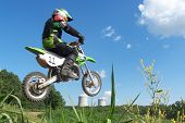 image of moto-x  - a young motocross racer jumping with a beautiful blue sky in the background.