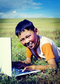 image of mongolian  - Mongolian Boy Laptop Grass Technology Connection Concept - JPG