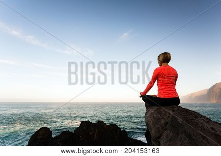 poster of Woman meditating in yoga pose ocean view beach and rock mountains. Motivation and inspirational fit and exercising. Healthy lifestyle outdoors in nature concept.