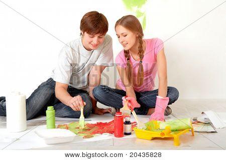 Foto des jungen Paares, die Farben mischen, während flache Verbesserung