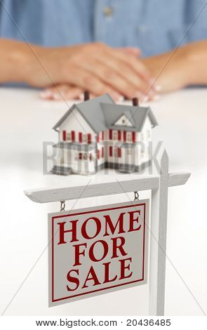 Woman's Folded Hands Behind Model House and Home For Sale Real Estate Sign In Front on White Surface.