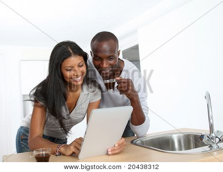 Young couple using electronic pad in kitchen