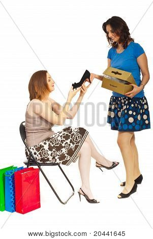 Smiling Clerk Showing New Shoe To Woman