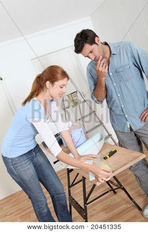 Couple choosing wallpaper color for new house