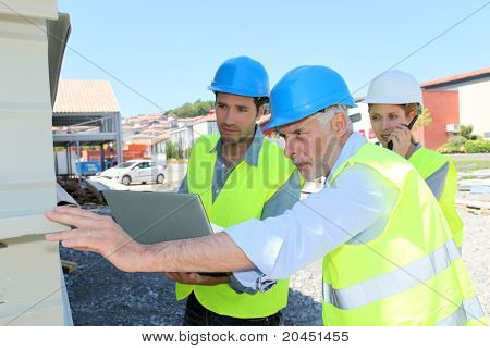 Construction workers checking building structure
