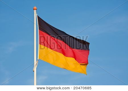 German Flag Blowing In The Wind Against A Blue Sky