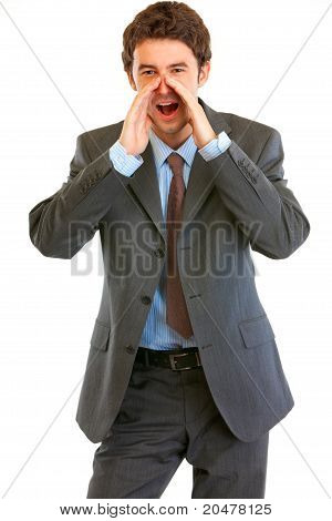 Cheerful modern businessman shouting through megaphone shaped hands isolated on white