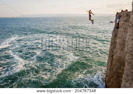 ACCO (ACRE), ISRAEL. September 16, 2017. Young Arab men jumping into the sea from the high fortification wall of the ancient Acco.