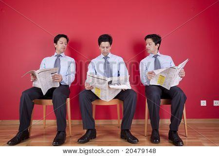 Tres empresario leerlo y leyendo el periódico emplazamiento en una silla