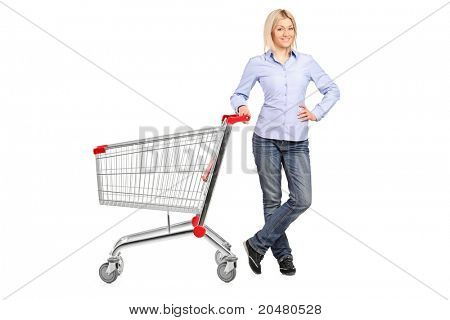 A smiling woman posing next to an empty shopping cart isolated on white background