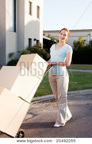 A woman with a stack of cardboard boxes on a trolly